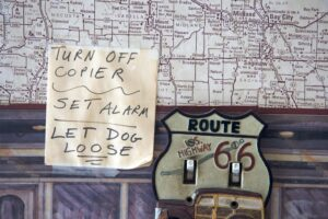Picture of a list of tasks taped to a large roadmap on wall, next to a novelty light fixture with Route 66 roadsign and old-fashioned wood-sided station wagon at bottom