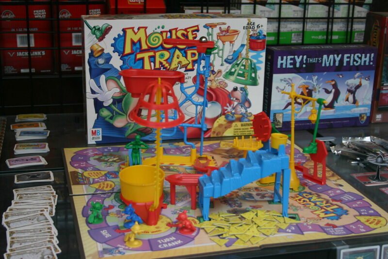 photo of a gameboard with the box top behind it, titled MouseTrap, and with a multicolored Rube Goldberg-type assemblage of plastic steps, gears, plunge pond and figurines set up on top of the board
