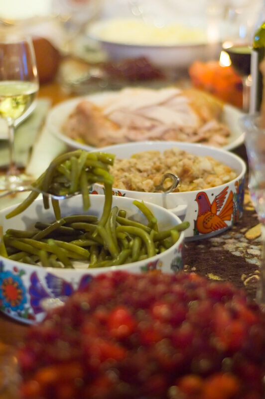 strip of dinner table showing dishes of unfocused red food in foreground (possibly cranberries), green beans sharply focused behind them, and then, in succession and gradually losing focus, bread stuffing and a platter of turkey slices and pieces