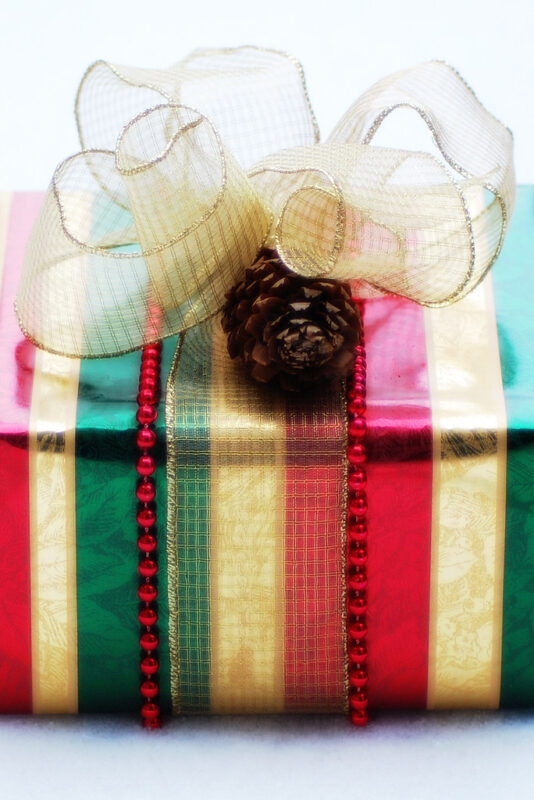 A single gift package, covered in striped red, cream, and green paper and decorated with two strings of small red beads and a wide semi-transparent cream ribbon tied at top in a large bow