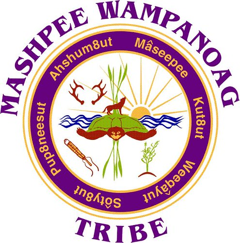 Official tribal seal with Mashpee Wampanoag Tribe lettering in purple around outside circumference, 2 golden lines circling inside that, around a purple strip containing several names, and a circle in center with deer antlers, a wolf or coyote, a sea turtle atop waving blue lines in front of a sun with long rays, grasses, a plant and ceremonial object, against a white background