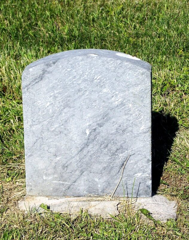 blank tombstone on a stone base, with green lawn behind