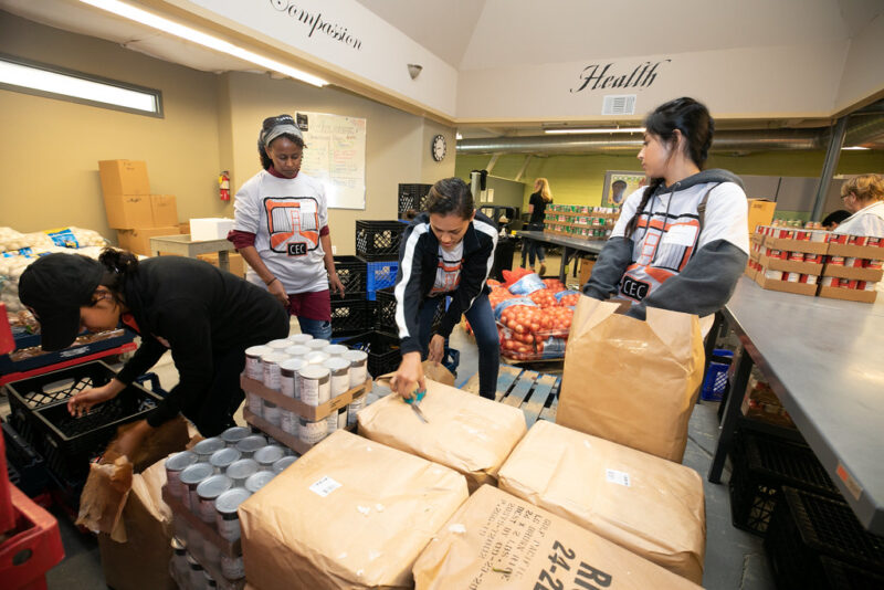 Food bank sorting area showing crates of canned food in foreground, being opened by 4 women, with a long table on the right side of frame, topped with more crates of canned goods in the background, and several large bags of onions or potatoes behind the women