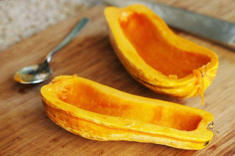 Two halves of cooked delicata squash lying on a wooden surface with tablespoon behind them.