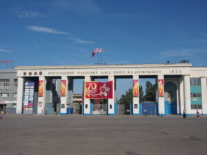 The entrance to a Russian tractor plant, eight white columns with blue bases, with a white horizontal beam over the columns carrying the name of the plant in Russian, with the year 1930 at the far right; four people, scattered, walking across the expanse of gray concrete in front of the plant