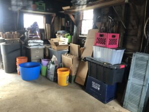 Same section of garage, showing items sorted out, all cardboard tied into orderly packs, buckets lined up, storage bins stacked neatly and trash bins ranged next to file cabinet; burlap screen rolled up and placed with tall stakes in far corner; flowerpots stacked in milk crates on a shelf above far window
