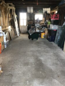 view of most of garage showing items ranged neatly along sides and at far end, with a lot of clear floor space in foreground and about 2/3 of the way up the photo