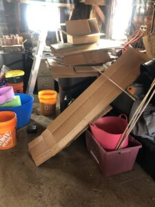 section of garage filled with jumble of multiple colors of buckets and garden equipment, flattened cardboard boxes, old burlap screens, bamboo stakes, and black garbage bins