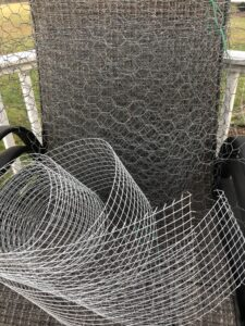 photo showing some hardware cloth, rolled up, with old chickenwire rolled up behind it