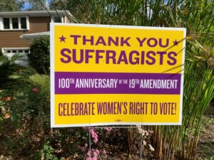 """close-up of yard sign, deep yellow background at top with purple lettering saying """"Thank you, Suffragists"""", then a strip of purple background with white lettering (""""100th anniversary of the 19th Amendment""""), and at the bottom another strip of purple lettering on yellow background (""""Celebrate women's right to vote!"""")"""
