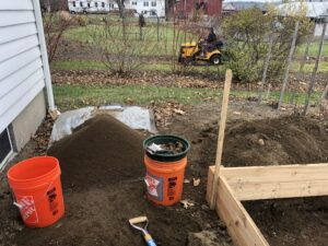 piles of soil next to corner of raised bed frame at lower right, with orange buckets in front of them at center and left, a bit of white clapboard wall to the left; lawns and shrubbery beds showing in background, with someone on bright yellow mower behind the screen of shrubs