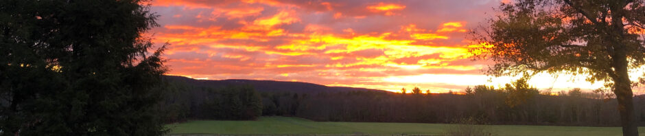 bright red-orange-yellow sunrise over distant hills and woods; moving towards foreground are green meadow, a wood-fenced paddock, small field with stubble, and a two-rail fence with evergreeen and leafless deciduous shrubs in front of it and flanked by fallen brown leaves; framed on left side by foreground evergreens and on right by oak tree with many brown leaves remaining on it