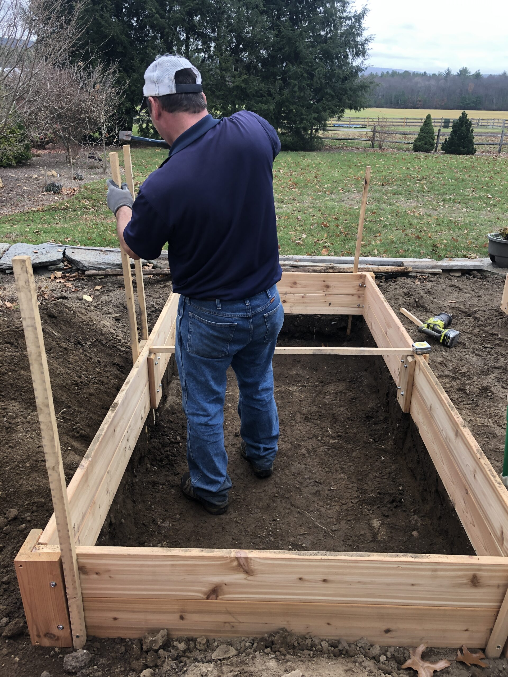 Man standing inside frame of raised bed, pounding in stakes; lawn, shrubs and trees in background