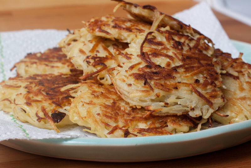Closeup of a pile of beautifully browned potato latkes on a white plate