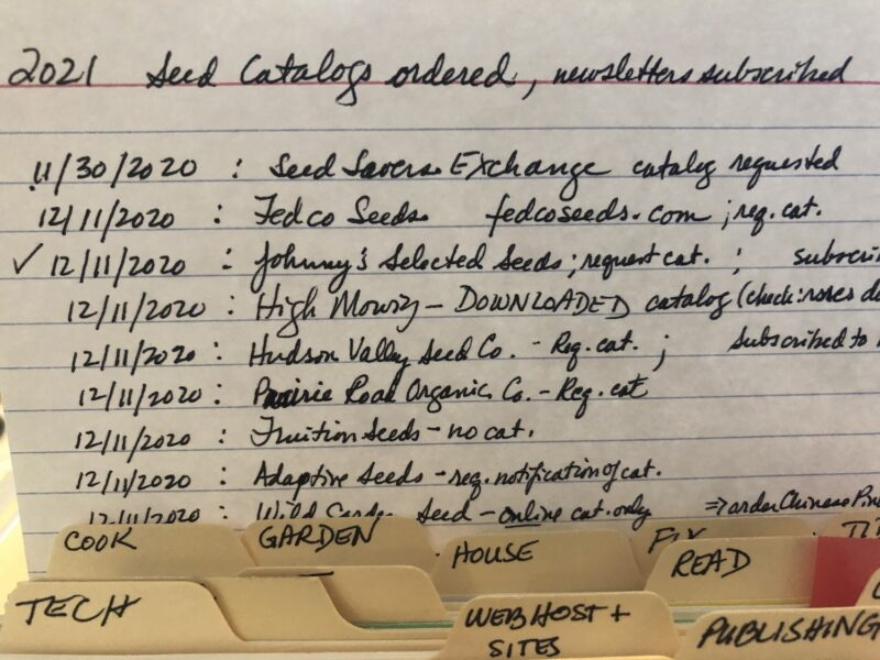 Photo shows the top part of an index card listing dates beside seed company names and notations on actions taken or not; underneath are the labels on index dividers listing various categories of tasks