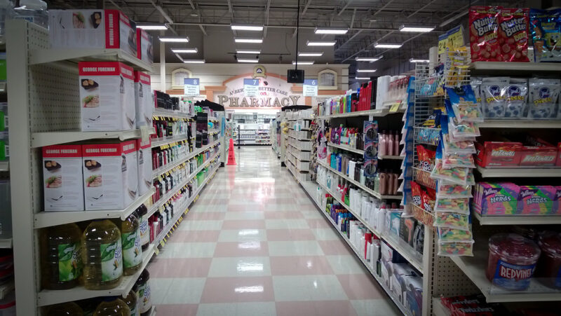 The long view down a supermarket aisle with a floor checkerboarded in pink and white squares; displaying shelves full of boxes and bottles, and several shelves full of candies at right foreground; at the back of the photo is a large sign for Pharmacy