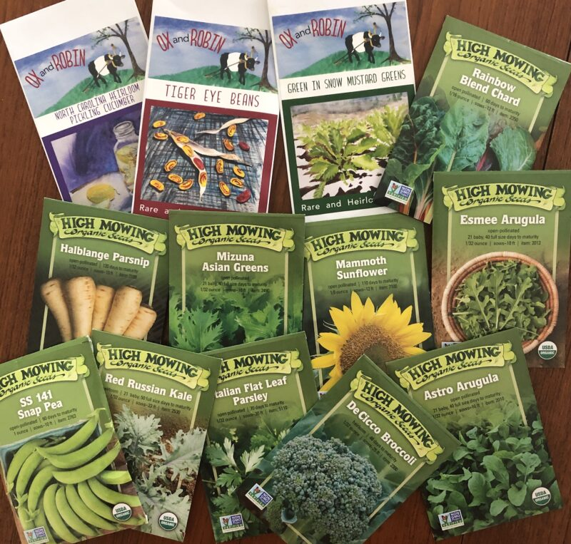 ten seed packets of various vegetables from High Mowing Organic Seeds and three packets from Ox and Robin