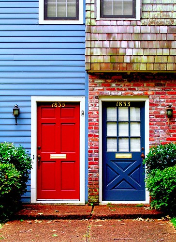 Portions of the fronts of two adjoining dwellings. On the left, light-blue clapboard with a red door, topped with the number 1835. On the right, a first-floor red brick front is topped by a greenish-brown shingled second floor; the door is dark blue with a nine-pane window in its top half; the house number 1833 is above the window. Both doors are framed in white, with small carriage-style lamps beside them and brass mail slots in their middle. Bushes flank the doors on the left and right side of the photo, and matching walkways of some reddish material lead the the two doors and their low stoops.