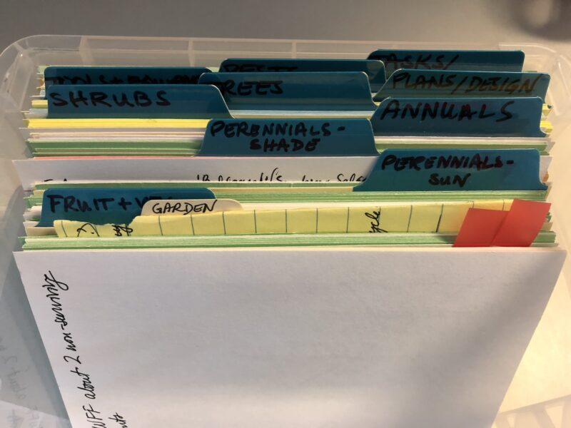 Closeup of card file box containing dividers labeled with garden categories: fruit & veg, perennials-sun, perennials-shade, annuals, shrubs, trees, plans/design, and three other dividers shaded so their headings are indecipherable; various colors of index cards can be seen ehind each divider.