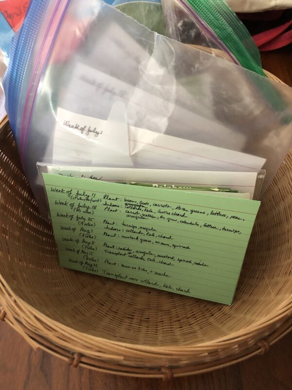 """rounded basket containing ziploc bags with dates showing inside each (week of July 11, week of July 18, etc.); in front of the bags is a green index card with vegetables listed after each """"week of"""" date from July 11 through Aug. 22"""