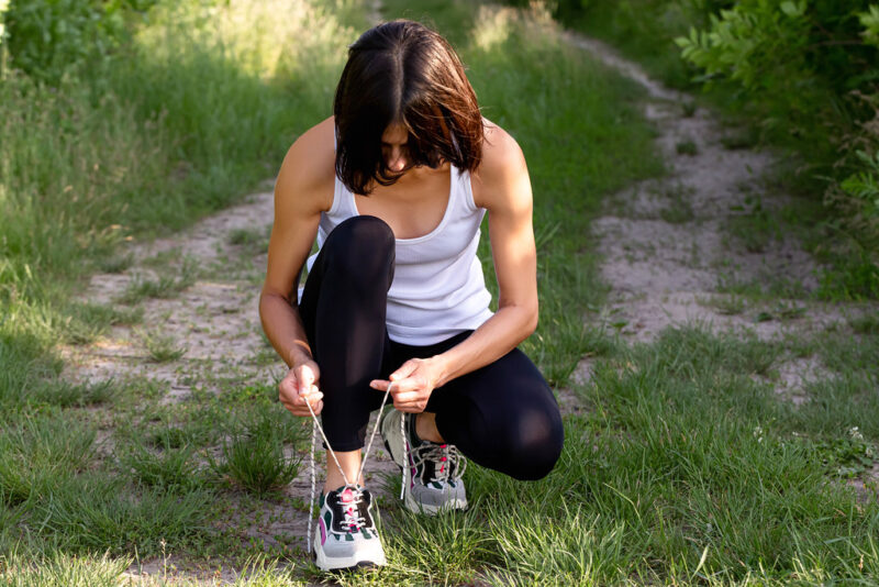 Woman in white tank top and black running rights squatting in middle of a sandy/grassy path tying very long shoelaces on her right shoe.