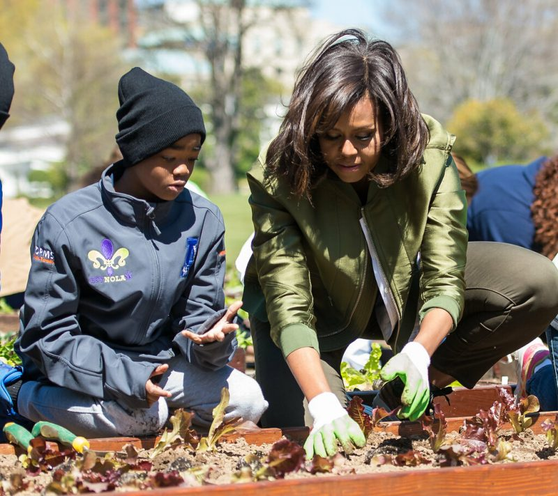 Michelle Obama, in olive green and on the right, and an unidentified child in blue jacket and dark watch cap on the left; both kneeling in front of a wood-edged garden bed with M.O. demonstrating planting a lettuce seedling; indistinct background with mostly bare trees and bushes and a partly sunny blue sky; yellowish green tinge of a bush in the background suggests early spring.